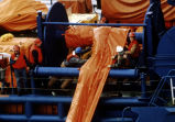 "Extreme closeup aerial of the ""Biehl Trader"" and deck hands deploying boom during boom..."