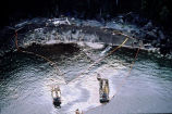 Aerial of a maxi-barge with water tanks and spill workers hosing a beach.