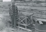 Alexie Moses posing with fish trap and sled in background, Eek, July 1956.