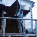 Georgie Wilson with his son Sonny. Georgie stands next to the bear he shot.