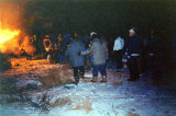 Igiugig community members walking around the Russian Orthodox Christmas New Years' bonfire.