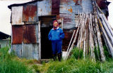 Mary Olympic in front of her old smoke house.