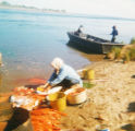 Blind Grandma splitting fish on the shore of Kvichak River.
