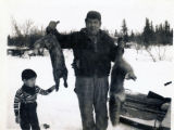 John D. Nelson with his son Howard. John is holding up a fox and an otter he caught.