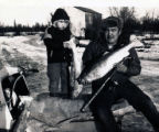 John D. Nelson with his grand son Kevin. John is holding up huge lake trout he caught.