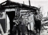 Butch Smith with friends posing for a photograph near a cabin.
