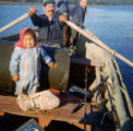 Georgie Wilson, middle, rowing his broken down boat from Kaskanak. His children Sonny, in bow, and...